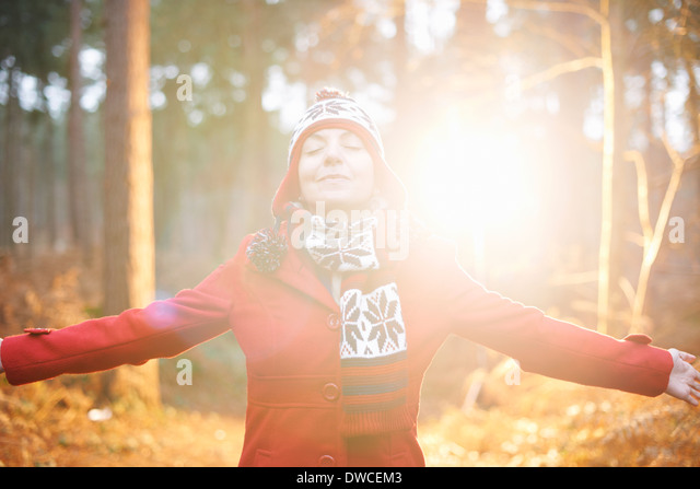Mature woman in hat and coat with arms out - Stock Image