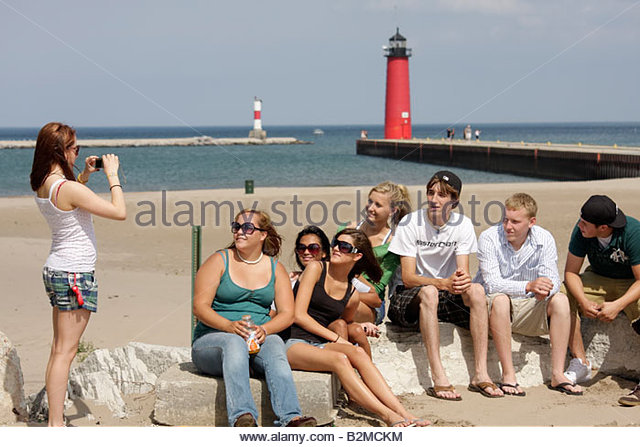 Wisconsin Kenosha Simmons Island Park Lake Michigan shore red lighthouse beach outing boy girl teens Asian friends - Stock Image