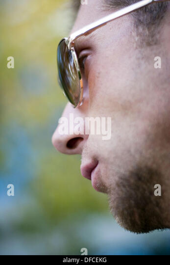 Side view of a young man wearing sunglasses, focus on eyes. - Stock Image