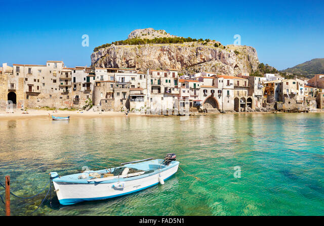 Fishing boat and medieval houses of Cefalu old town, Sicily, Italy - Stock-Bilder