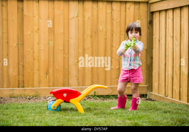 Young girl with toy wheelbarrow putting on gardening gloves - Stock Image