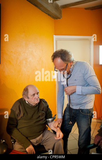 TAKING AN ELDERLY PERSON'S PULSE - Stock Image