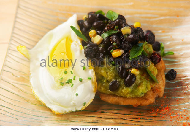 Avocado tostada, with black beans and fried egg. - Stock Image