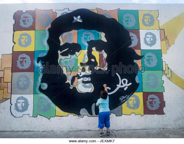 A boy reaches up to a mural portrait of Che Guevara in Capdevila Street in the La Habana Vieja district. - Stock Image
