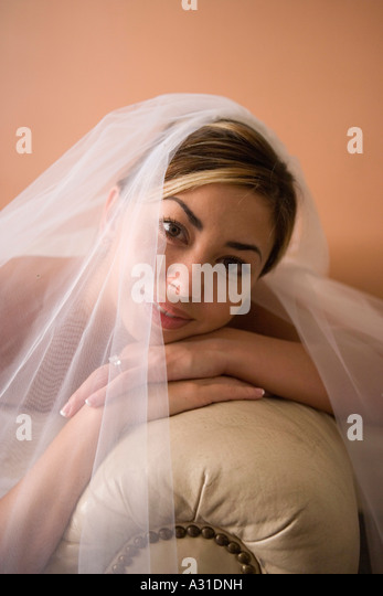 Portrait of bride leaning on leather sofa - Stock-Bilder