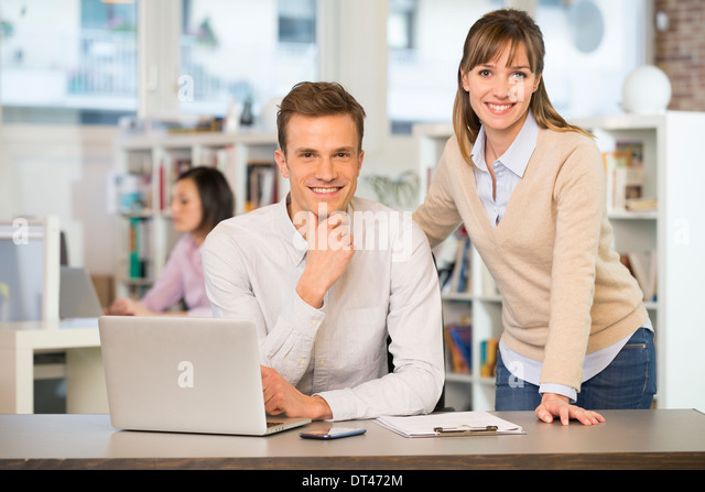 Businesspeople happy desk computer casual - Stock Image