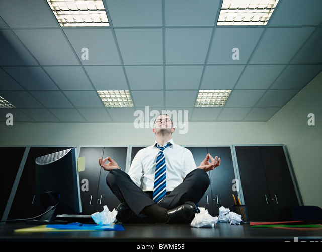 Mature businessman sitting on desk in lotus position. Horizontal shape, full length, Copy space - Stock Image