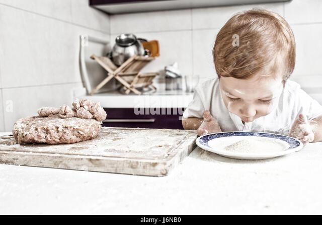 Baby boy preparing meatballs. He is looking the plate full of bread crumbs - Stock Image