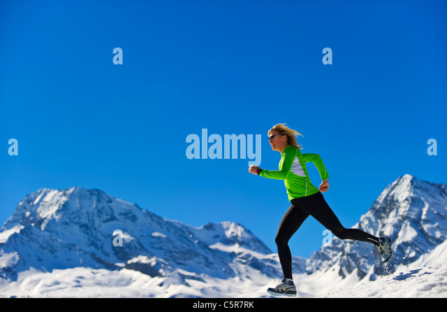 A woman jogging fast over snowy mountains. - Stock-Bilder