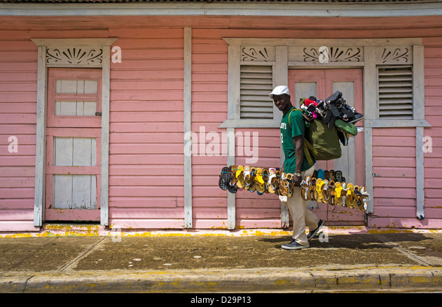 Man selling shoes walks past little pink houses in Otra Banda, La Altagracia province, Dominican Republic - Stock Image
