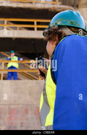 Workers using walkie talkies on dry dock - Stock Image
