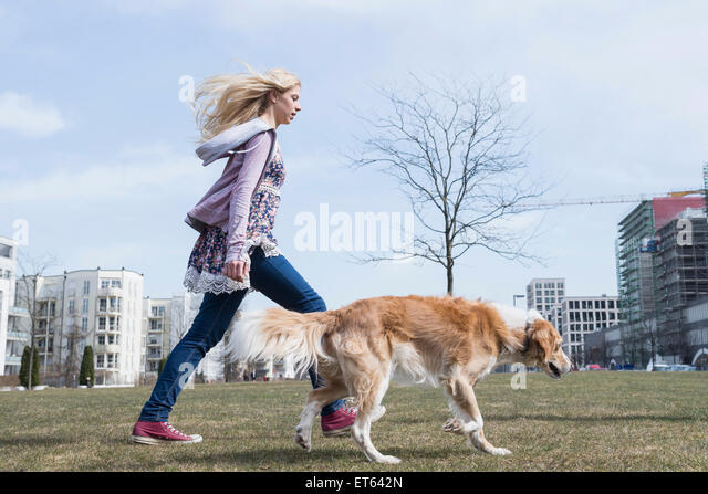 Side profile of teenage girl walking in park with dog, Munich, Bavaria, Germany - Stock Image