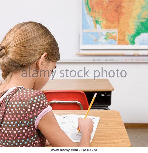 Girl doing school work in classroom - Stock Image