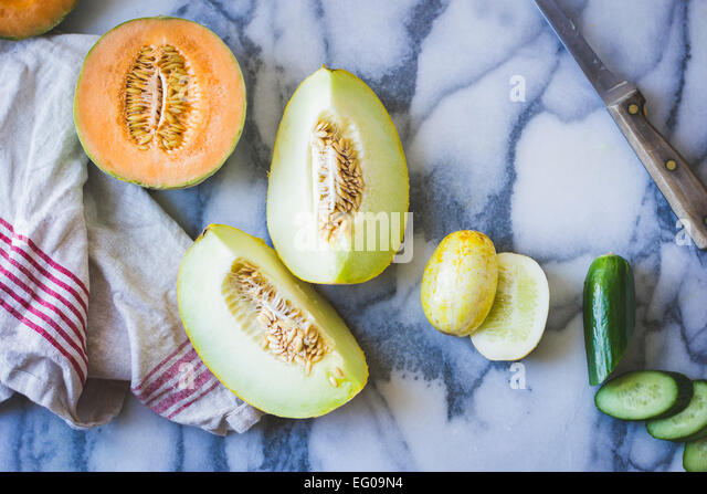 Cucumber and melons on a work surface - Stock Image