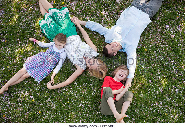 Family laying in grass together - Stock-Bilder
