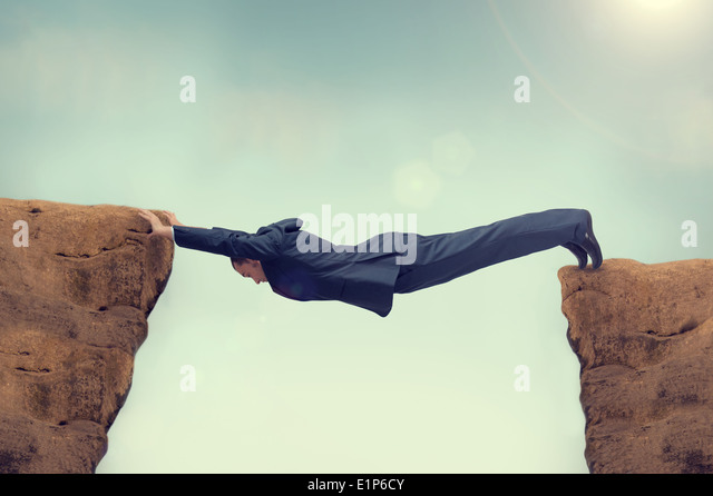businessman overstretched between a rock and a hard place - Stock Image