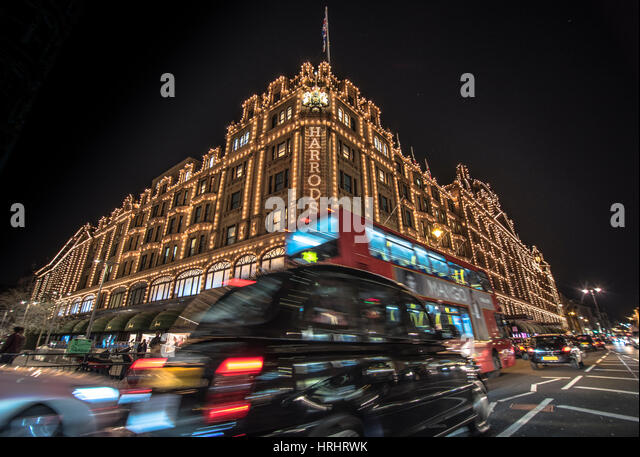 A London taxi and a London bus drive past Harrods, London, England, United Kingdom - Stock-Bilder