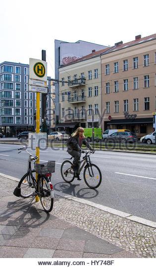 Parked bike at bus station, city Berlin Mitte, woman cycling on road female biker street germany, everyday street - Stock-Bilder