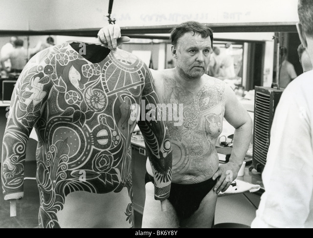 ROD STEIGER in makeup for 1969 Warner film The Illustrated Man with the artwork for the tattoo he has had painted - Stock Image