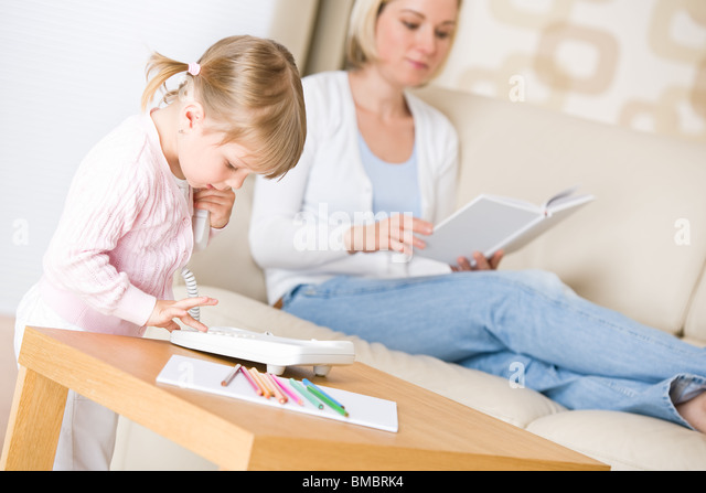 Little girl dial number on phone in living room, mother in background - Stock Image