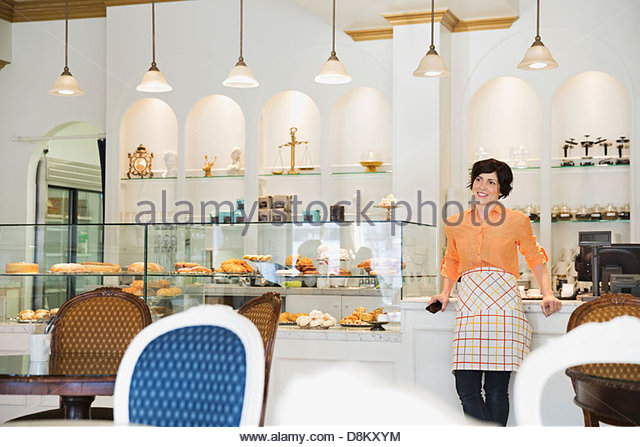 Female small business owner working in coffee shop - Stock Image