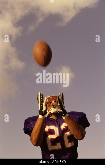 Low angle view of an American football player catching a ball - Stock Image