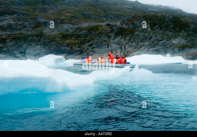 Passengers on an open boat, Angmagssalik Fjord, East Greenland - Stock Image