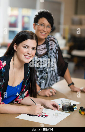 Portrait of young seamstress painting fashion design in workshop - Stock Image