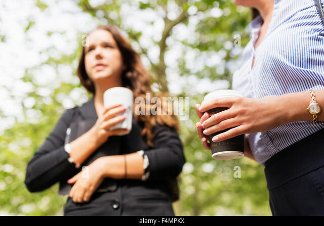Low angle view of businesswoman holding coffee outdoors - Stock Image