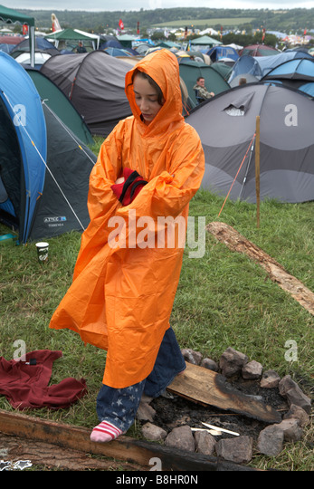 Glastonbury Festival 2007, teenage girl stands in campsite in bad weather wearing free Orange rain mac - Stock-Bilder