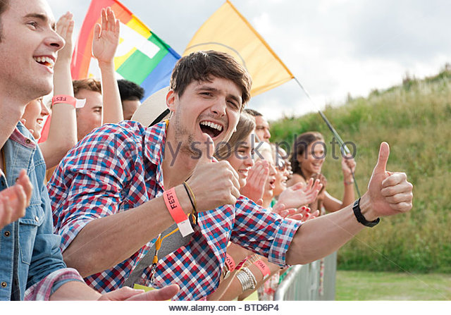 Young people cheering at festival - Stock Image