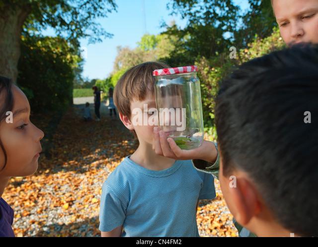 Boy showing jar to children - Stock Image