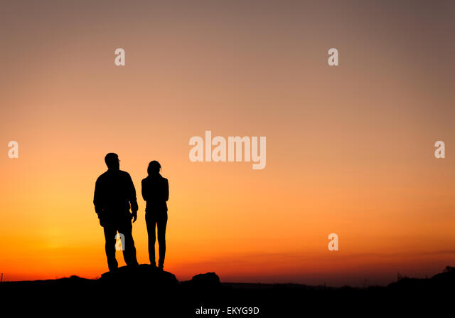 Silhouette of happiness family against beautiful colorful sky. Summer Sunset. Landscape - Stock Image