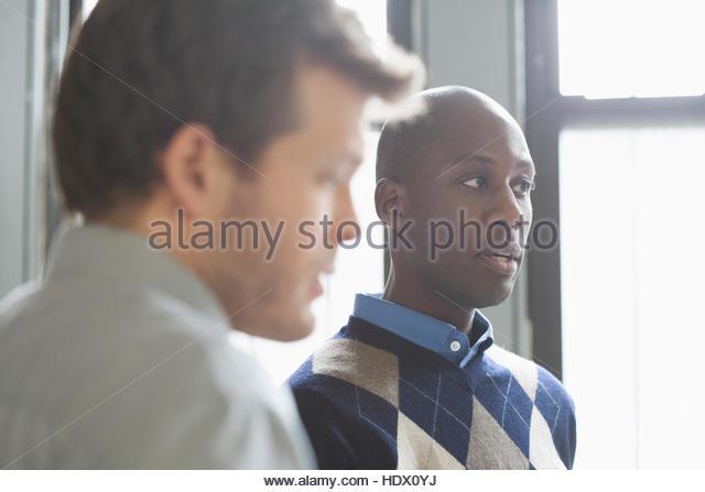 Businessmen talking in office - Stock Image
