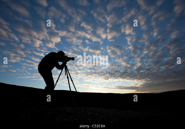 Photographer silhouetted as he photographs on top of Blueberry Hill near Wonder Lake, Denali National Park and Preserve, - Stock Image
