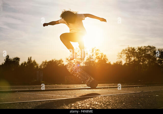 Young man on skateboard in backlight - Stock Image