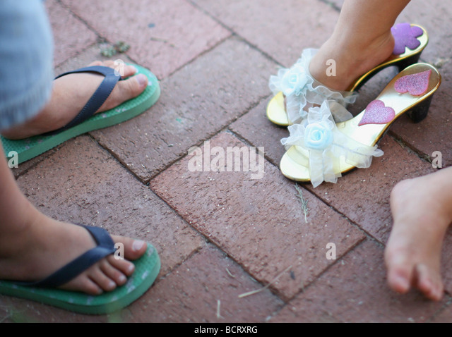 Low section of two children wearing slippers and sandal - Stock-Bilder