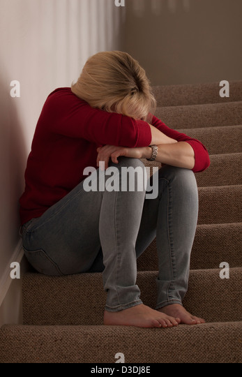Blonde woman sitting alone on the steps, head bowed forward upset or crying. - Stock Image