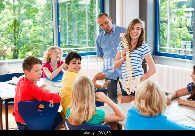 Schoolgirl holding spinal column model in class - Stock Image