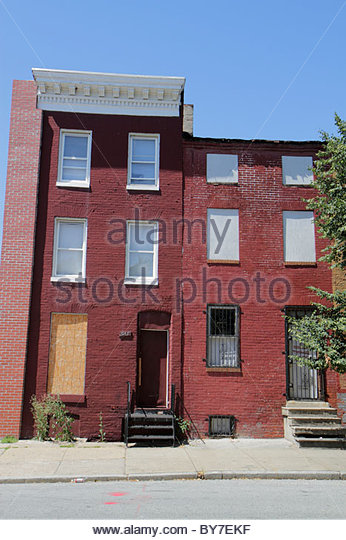 Maryland Baltimore West Lexington Street row house red brick boarded up blight urban decay abandoned building poverty - Stock Image