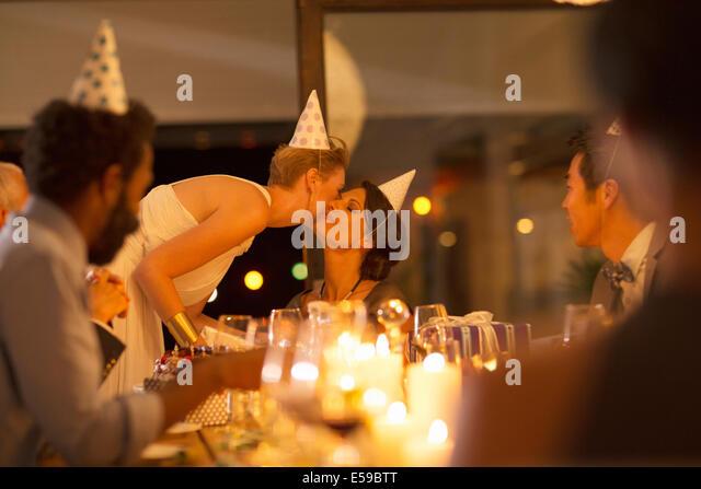 Woman kissing friend?s cheek at birthday party - Stock-Bilder
