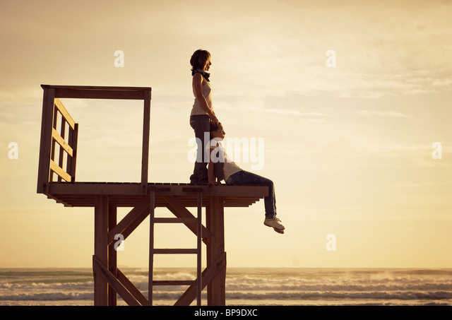 tarifa, cadiz, andalusia, spain; a mother and daughter on a wooden tower on los lances beach at sunset along costa - Stock Image