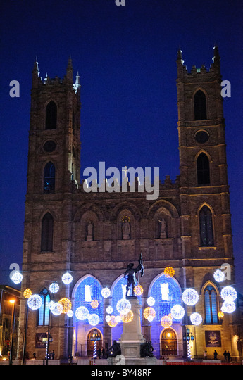 Lights decorate the Place D'Armes in front of the the Basilique Notre-Dame de Montreal. - Stock Image