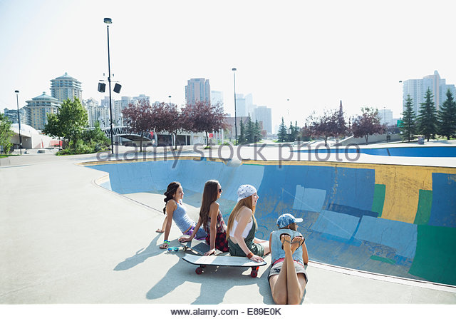 Teenage girls sitting at edge of skateboard ramp - Stock Image