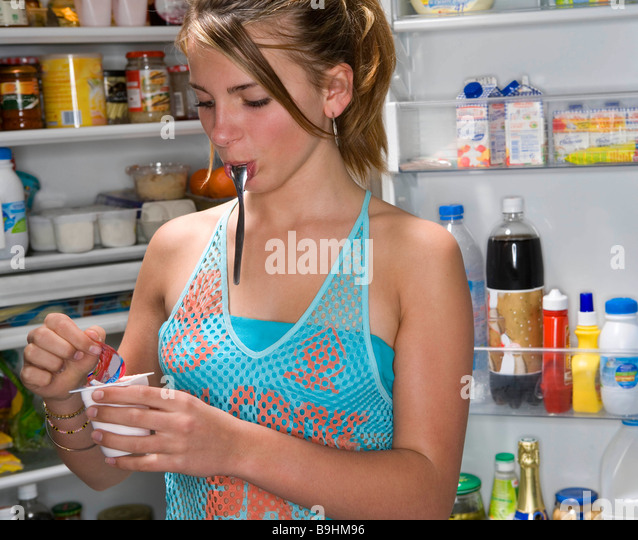 Teen girl opens yogurt food - Stock Image