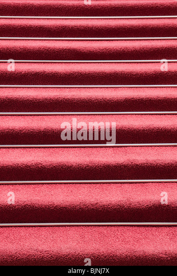 Abstract image of red carpet on symmetrical stairs - Stock Image