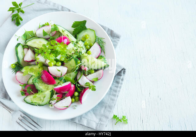 Healthy spring vegetables salad with radish, cucumber, green peas and sprouts, diet, vegetarian, vegan, organic, - Stock Image