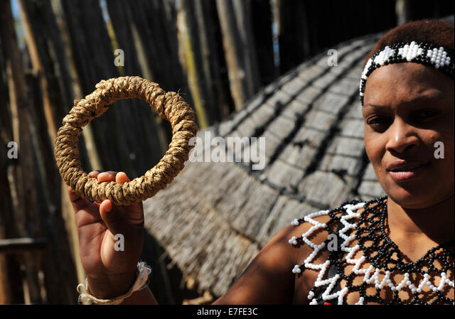 Zulu maiden showing grass ring used to balance clay pots traditionally carried on head while walking Shakaland South - Stock-Bilder