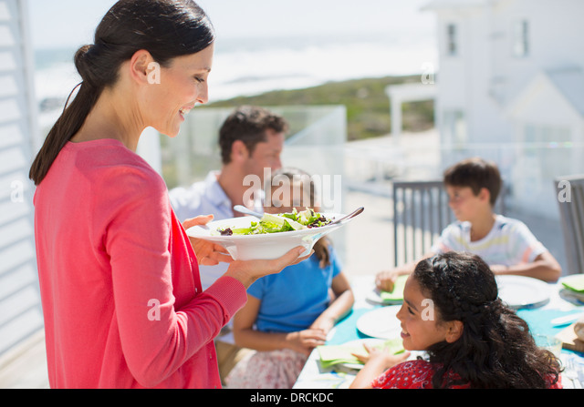 Family eating lunch at table on sunny patio - Stock Image
