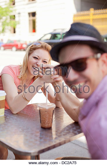 Young couple arm wrestling in cafe - Stock Image